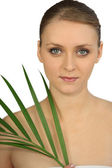 Bust shot of graceful blue-eyed blonde and plant — Stock Photo