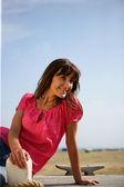 Donna seduta sul boardwalk — Foto Stock
