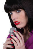 Female singer caressing a micro — Stock Photo