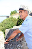Grey-haired man visiting port town — Stockfoto
