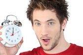 Shocked man with alarm clock — Stock Photo