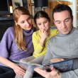 Stock Photo: Young family going through photo album