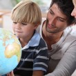 Little boy learning about the world with the help of his parents — Stock Photo