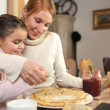 Loving mother making crepes with little girl — Stock Photo