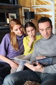 Young family going through photo album — Stock Photo