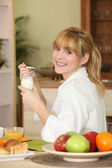 Blonde woman taking yogurt — Stock Photo