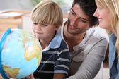 Little boy learning about the world with the help of his parents — Стоковое фото