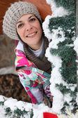 Woman behind snowy tree — Stock Photo