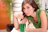 Attractive brunette drinking mint cordial — Stock Photo