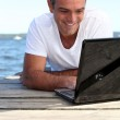 Man using his laptop on jetty — Stock Photo