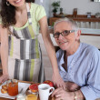 Senior woman being served breakfast at home — Foto de Stock