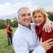 Couples hugging in a field — Stockfoto