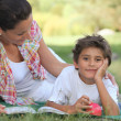 Mother and son lying on the grass - Stock Photo
