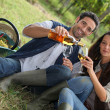 Couple with wine in the field — Stockfoto