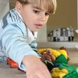 Stock Photo: Young boy playing with toys