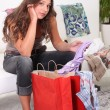 Stock Photo: Womlooking at her purchases