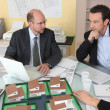 Architects gathered around a desk exchanging ideas — Stock Photo