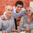 Elderly couple and grandson in restaurant — Stock Photo