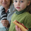 Little girl eating sandwich with mother — Stock Photo
