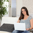 Stock Photo: Woman sitting on couch with computer