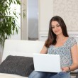 Woman sitting on couch with computer - Stock Photo