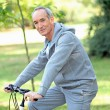 Elderly man riding his bike — Stock Photo