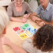 Family playing board game together - Stock Photo