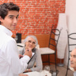 Mature couple at restaurant with waiter — Stock Photo #9308836