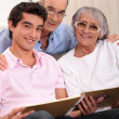 Grandparents and grandson looking through family album — Stock Photo #9309063