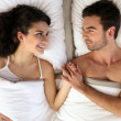 Young couple holding hands in bed — Stock Photo