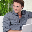 Man on a sofa with a laptop — Stock Photo