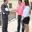 Couple shaking hands with an agent — Stock Photo
