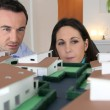 Couple looking at a model of a housing estate — Stock Photo #9309835