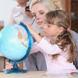 Stock Photo: Mother and daughter looking at globe