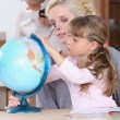 Foto Stock: Mother and daughter looking at globe