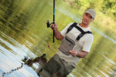 Oblique image of a fisherman on a river — Stock Photo