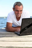 Man using his laptop on jetty — Stockfoto