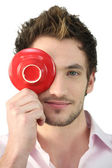 Young man holding a saucer in front of his eye — Stock Photo