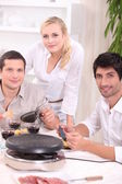 Three friends eating a raclette — Stock Photo