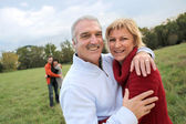 Couples hugging in a field — Stock Photo