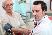 Doctor taking tension to senior woman — Stock Photo