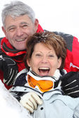 Senior couple having a great time skiing — Stock Photo