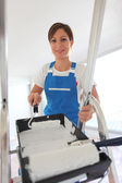 Female decorator climbing ladder — Stock Photo