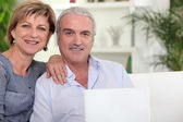 Couple with computer on couch — Stock Photo