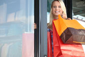 Woman leaving store with shopping bags — Stock Photo