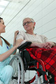 Nurse with elderly woman in wheelchair — Stok fotoğraf