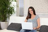 žena sedí na gauči s počítačem — Stock fotografie