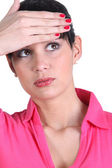 Young woman touching her forehead — Stock Photo