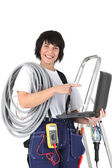 Female electrician with laptop and voltmeter — Stock Photo