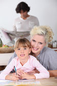 Mother with girl doing homework — Stock Photo